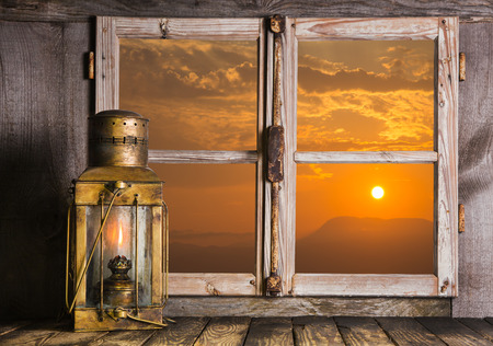 sill: Old copper lantern on Windows sill: view outdoor when the sun rise up. Concept for dreams, feelings or mourning. Stock Photo