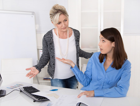acoso laboral: Mujer de negocios que tiene problemas en el acoso laboral, mobbing, herassment en el lugar de trabajo en virtud de colegas Foto de archivo