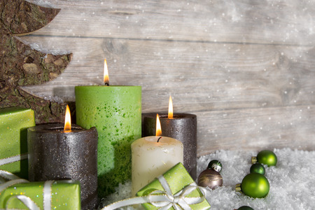Four burning advent candles in green and brown on wooden grey background. photo