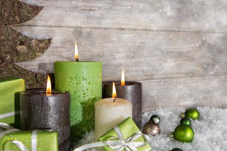 bougie coeur: Quatre bougies allumées de l'Avent en vert et brun sur fond gris en bois. Banque d'images