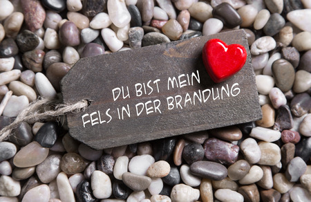 feeling good: You are solid as a rock: german text for lovers with red heart on wooden sign. Idea for a greeting card.