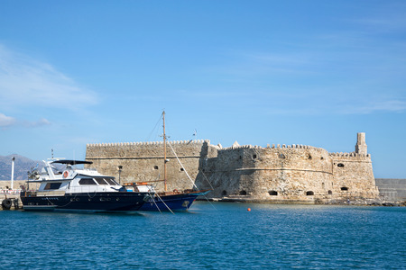 Greek island crete in the cyclades  sightseeing on the old port with fort and boats on blue sky  Stock Photo