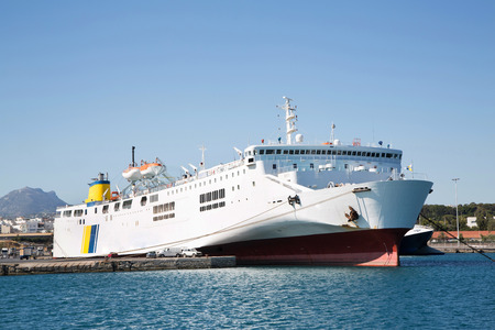 ferries: Big and large ferry boat or cargo ship in the port with blue sky. Stock Photo