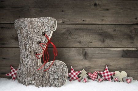 Xmas greeting card with santa boot in red and white colors on wooden background with snow. Idea for christmas decoration.