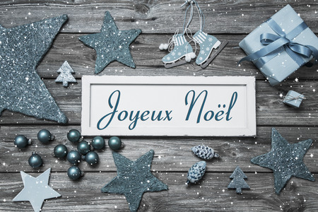 french text: Merry Christmas card in shabby chic style in blue and white with french text on wooden board.