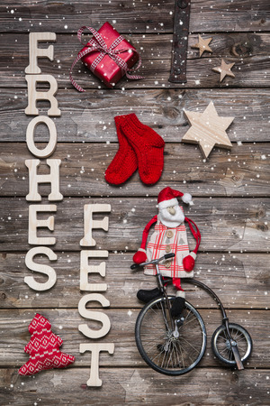 Merry christmas card with german text on wooden background with red santa on a bicycle. Vintage style. photo
