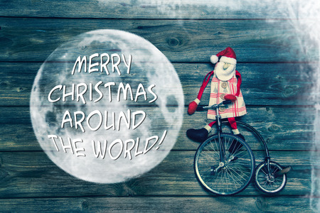 Merry christmas around the world - greeting card with english text decorated with wood, santa and an old unicycle. photo