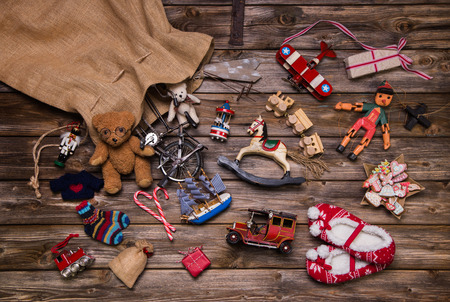 Christmas memories in childhood: old used and tin toys on wooden background for gifts.