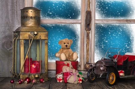 juguetes antiguos: Decoración vieja de la Navidad en el alféizar de la ventana de madera con el vintage y juguetes nostálgicos.