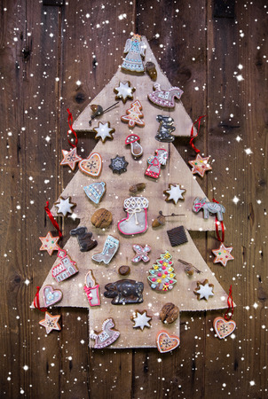 whittle: Handmade carved christmas tree decorated with gingerbread, stars and hearts on wooden background.
