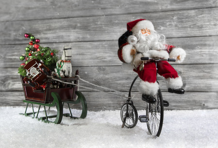 Funny christmas greeting card with Santa on a bike pulling a slide in the snow. photo