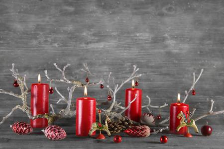 corona de adviento: Cuatro quema de velas de cera de color rojo sobre fondo gris advenimiento de madera. Foto de archivo
