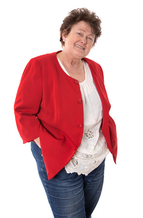 humorously: Portrait of an older retired happy woman isolated on white wearing a red jacket.