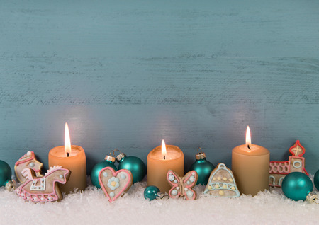 Shabby chic christmas or advent wooden background in mint green or blue color with four burning candles in gold as decoration. photo