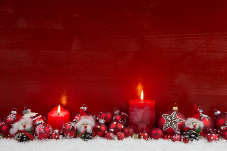 Red wooden christmas background with two burning candles - classic decoration.
