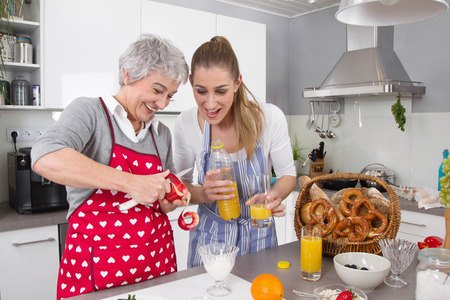 gray haired: Happy mother and daughter preparing breakfast together  Stock Photo