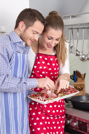 meat lover: Young fresh married happy couple in the kitchen eating sausages. Stock Photo