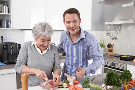 Hôtel maman jeune homme et femme plus âgée cuisiner ensemble rôti de porc