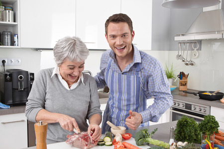 Hotel mama  young man and older woman cooking together roast pork  Stock Photo