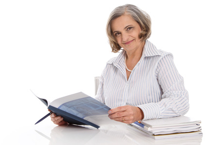gray haired: Portrait of an older smiling businesswoman sitting at desk with balance sheet