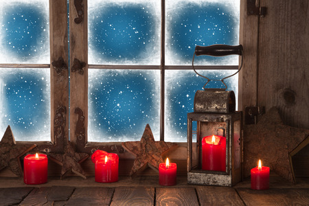 winter window: Christmas decoration with red burning candles and a lantern for a background. Stock Photo