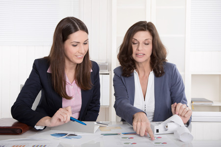 Two business woman analyzing balance sheet sitting at desk
