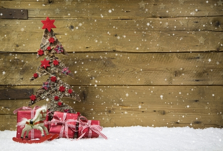 whittle: Christmas tree with red presents and snow on wooden snowy background for a greeting card.