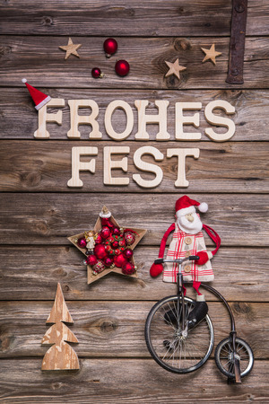 Merry Christmas Frohes Fest in german letters. Greeting card with wood, red and white. photo