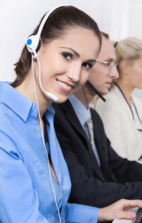 Happy business woman on the phone in a call center wearing blue blouse. photo