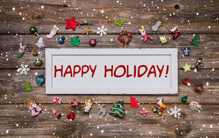 Happy Holiday - christmas congratulatory card in different colors on wooden background. photo
