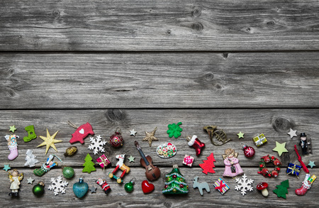 Shabby chic wooden grey christmas background for a greeting card with colored miniatures. photo