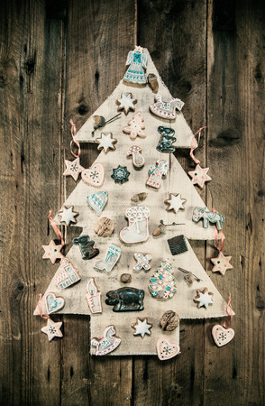 whittle: Christmas decoration: wooden carved tree decorated with gingerbread and cookies.