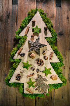 whittle: Handmade christmas tree of wood on wooden background with natural decoration of the forest.