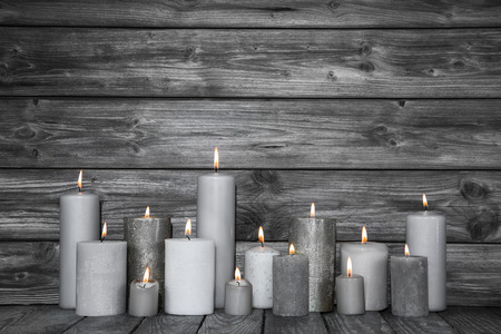 Burning candles in white and grey on wooden shabby chic background.Idea for a card for mourning, death or christmas. Stockfoto