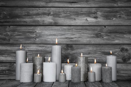 Brandende kaarsen in wit en grijs op houten shabby chic achtergrond. Idee voor een kaart voor rouw, dood of Kerstmis.