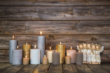 Christmas greeting card with many candles and angels on wooden background. photo