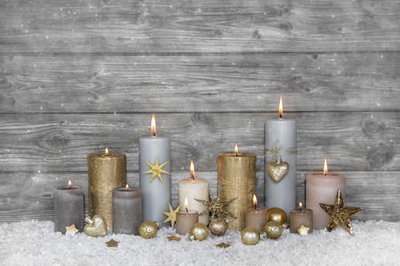 Merry christmas greeting card: wooden grey shabby background with candles. Banco de Imagens