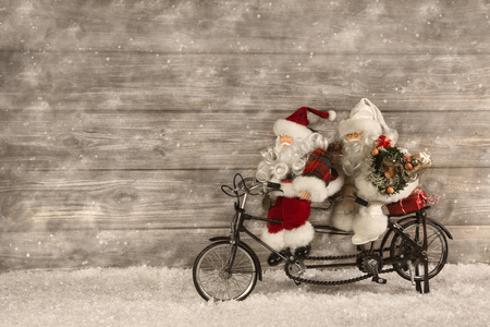 Two santa claus in hurry for buying christmas presents decorated on wooden background in vintage style.