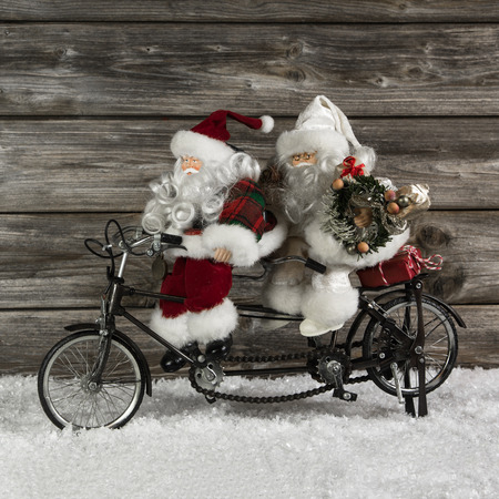 Two funny santa claus on a tandem in hurry for christmas shopping. Witty advent decoration for december.