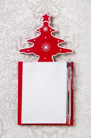 wishlist: Christmas wishlist: white and red writing pad with a tree of wood.