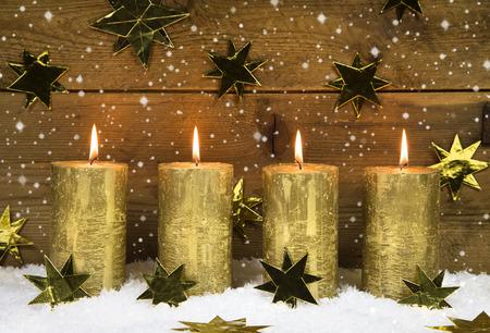 corona de adviento: Cuatro velas de oro ardientes de navidad en el fondo de madera rústica.
