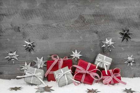 Des cadeaux de Noël en rouge et argent sur fond de bois gris en bois. Banque d'images