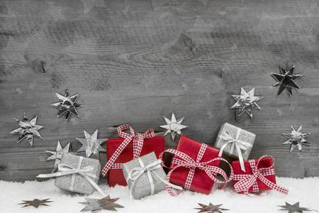 Vánoční dárky v červené a stříbrné barvě na dřevěné šedé dřevěné pozadí. Reklamní fotografie