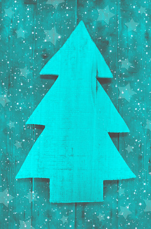 whittle: Christmas background in turquoise green color of a handmade carved tree with snow.