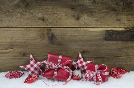 Presents for christmas in red white checkered color on wooden old country style background.