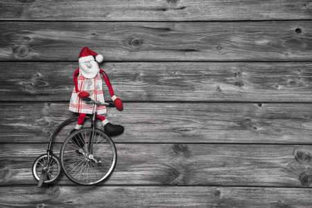 Funny red santa claus on wooden grey background in hurry for buying christmas presents sitting on a old bike  photo