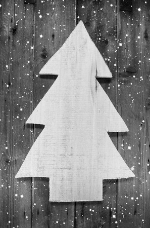 christmas symbol: Wooden grey and white christmas tree in shabby style on a wood snowy background for a greeting card