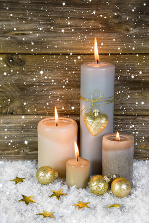 Festive christmas decoration in gold and white  four red burning advent candles on wooden background  photo