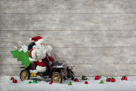 Santa claus in rush with his car  christmas shopping stress  Decoration with old vintage tin toys on wooden background