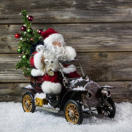 Santa claus in rush with his car  christmas shopping stress  Decoration with old vintage tin toys on wooden background  photo